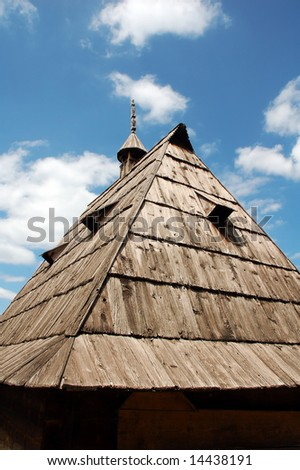 An old wooden roof on a primitive country house with a wooden with a decorative chimney