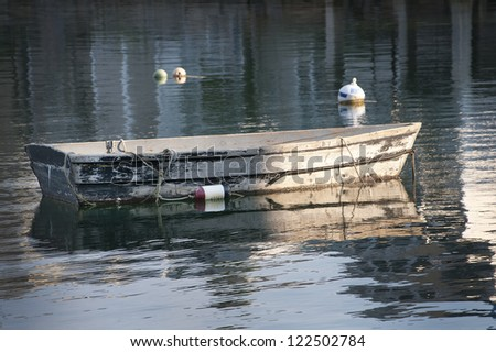 An old wooden rowboat is anchored in historic Rockport Harbor, Massachusetts.