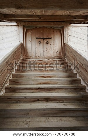 An old wooden staircase leads to the doors upwards.