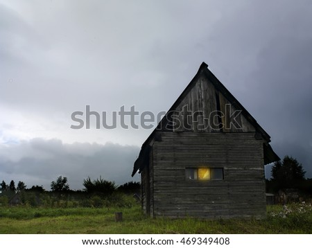 An old wooden summerhouse with one window illuminated, outdoors digitally altered shot