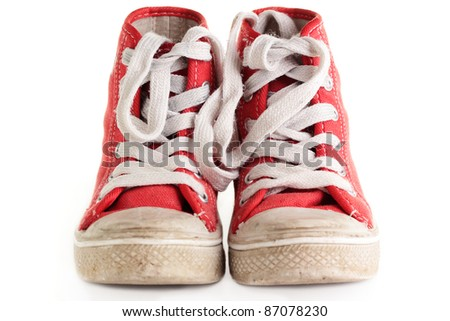 An old worn pair of children's sports shoes/trainers on a white background.