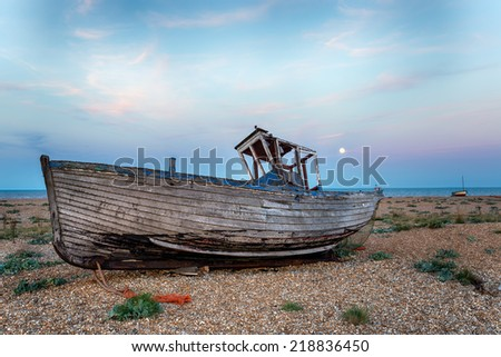 An old wrecked boat on a shingle beach under a full moon