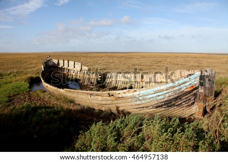 An old wrecked whaler lies in the saltmarshes in East Anglia, England amongst a bleak and empty landscape