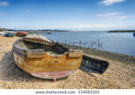 An old wrecked wooden boat on the shore at Poole in Dorset
