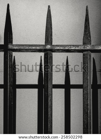 An old wrought iron fence and its shadow on a wall. - stock photo