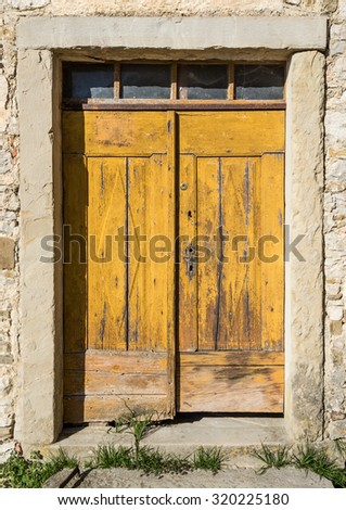 an old yellow ragged shabby wooden door - stock photo