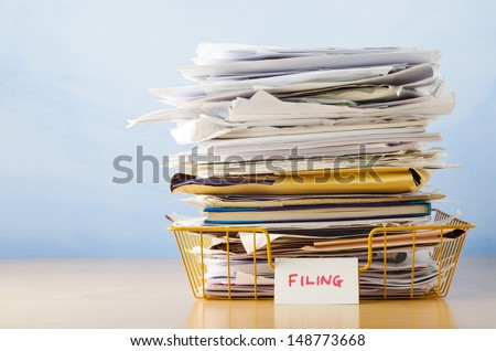 An old yellow wireframe filing tray, piled high with documents and folders, on a light wood veneer desk against light blue background. - stock photo