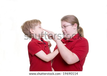 An older child pokes a younger child in the nose