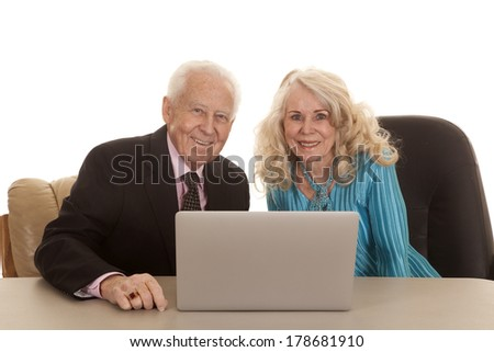 An older couple business people working together on a laptop. - stock photo