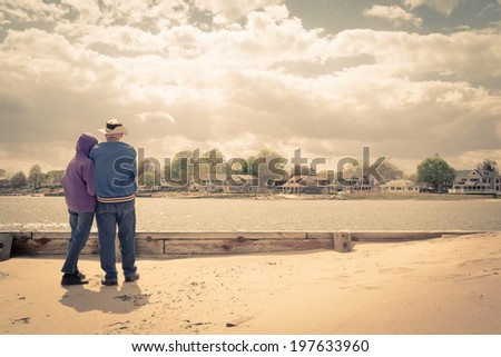 An older couple on the beach looking across the water at beautiful waterfront homes.  Vintage effect applied. - stock photo