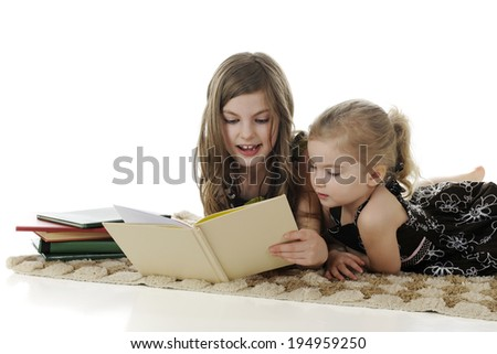 An older elementary girl reading a story to her interested little sister.  On a white background, with space on the left for your text. - stock photo