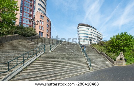 An older man and a woman climbing together on a wide and tall concrete stairs on a beautiful spring day. In the background are colorful tall buildings. - stock photo