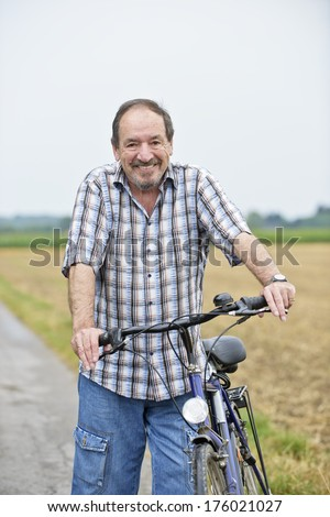 An older man holding handles on a bike.