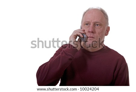 An older man isolated on white talking on a cell phone with a sad expression