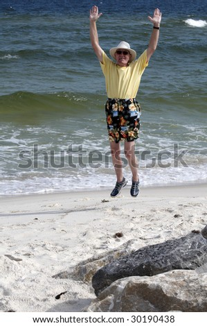 An older man jumping for joy on the beach. - stock photo
