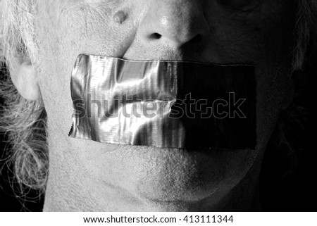 an older man's mouth is covered and taped closed with duct tape, side lit with half of face in shadow, finished in black and white. - stock photo