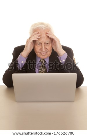 An older man sitting at a laptop computer with his hands on his head. - stock photo