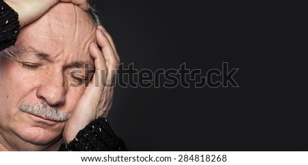 an older man suffering from a headache on dark background - stock photo