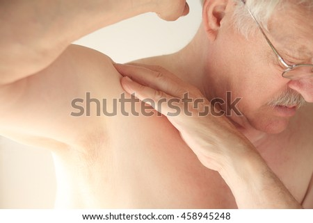An older man tries to move his shoulder without pain. - stock photo