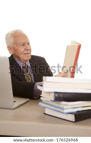 An older man with a computer and a stack of books reading. - stock photo
