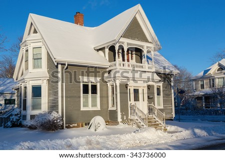 An older style North American home after a snowfall. - stock photo