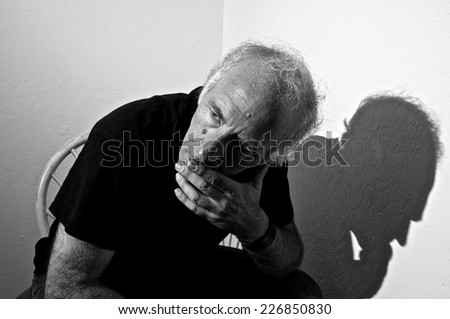 An older white male is sitting in a corner on a chair leaning forward and looking away in thought. - stock photo