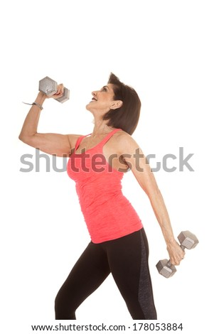 An older woman with a smile on her face working out with weights.