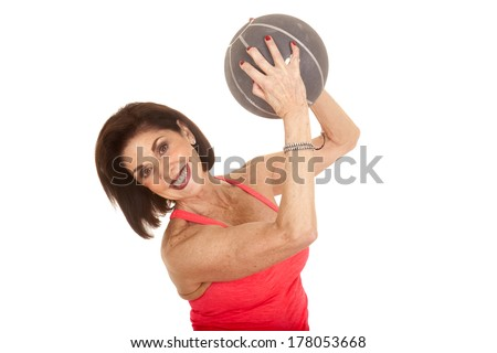 An older woman working out with a weighted medicine ball.