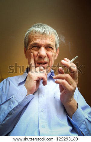 An older worried man smoking