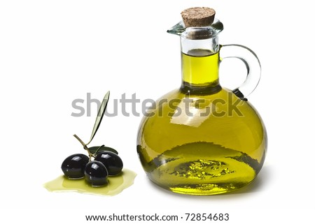 An olive oil pourer and some olives isolated on a white background.