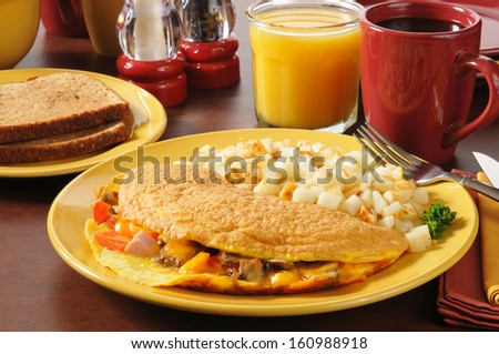 An omelet with ham, cheese, tomatoes and mushrooms and fried potatoes - stock photo