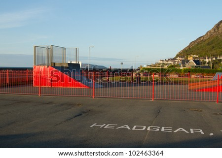 An open air skatepark with a red painted ramp and railings and a sign painted on the floor reading 'HEADGEAR'.