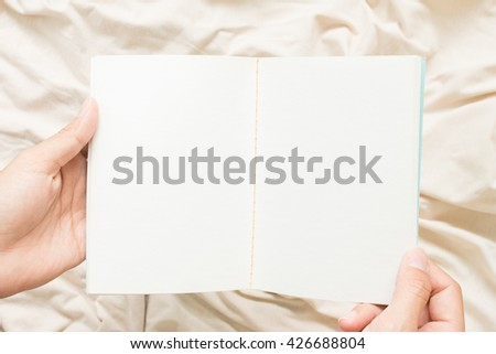 An open blank no lined  notebook on hands. - stock photo
