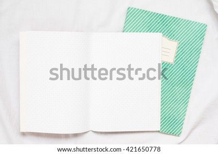 An open blank polka dot notebook on green notebook on white fabric background . - stock photo