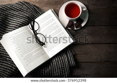 An open book, a cup of tea, glasses and a blanket on the wooden background - stock photo