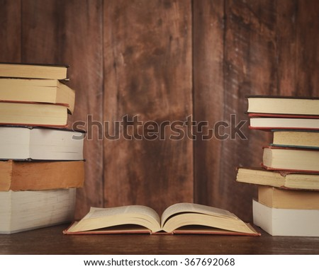 An open book with stacked books beside it are on a desk with a wooden blank background for copyspace or text.
