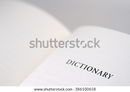 An open book with the word dictionary reading on the right page, copy space available. - stock photo