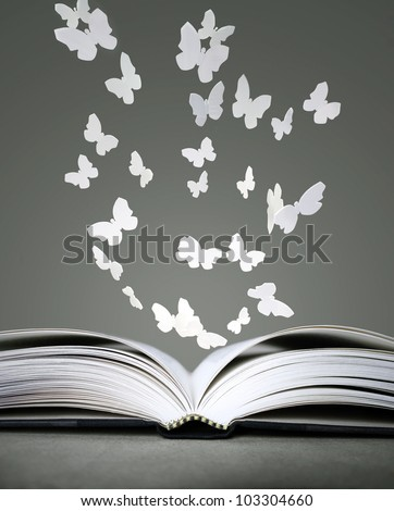 An open book with white butterflies on grey background