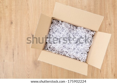 An open box with filling material inside lying on a laminated wooden floor, top view with copy space. - stock photo