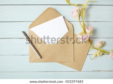 An open brown envelope with letter and writing pen on a blue wooden desktop background