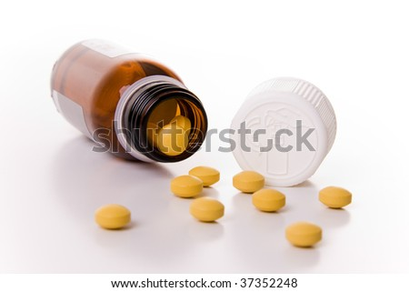 An open container with yellow pills - Selective focus - stock photo