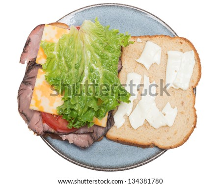 An open faced sandwich on a plate, isolated on a pure white background. Sandwich made with Roast beef, colby jack cheese, lettuce, tomato, and mayonnaise on whole wheat bread. - stock photo