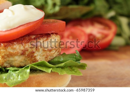 An open grilled turkey burger with salad and mayo. - stock photo