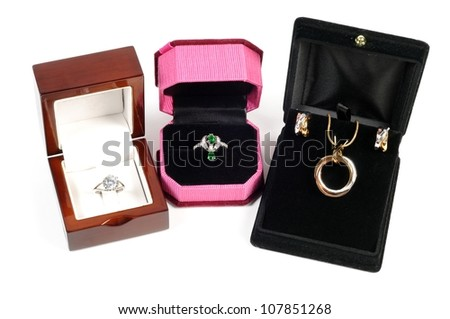 An open jewlery boxes with gold and platinum  jewelry sets on a white background - stock photo