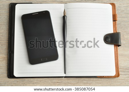 An open notebook displayed with a smart phone and a fountain pen on a wooden table - stock photo