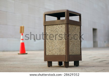 An open public space with brown garbage can in focus. - stock photo