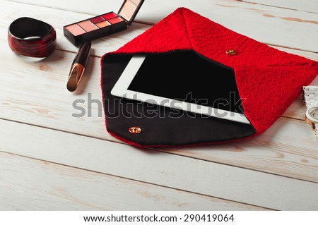 An open red lady's bag with tablet computer in a white wooden table. Near the handbags are women's accessories. Mascara, eye shadow, watch and bracelet - stock photo