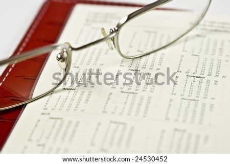 An open red organizer displaying a full calendar year with some of the months in focus; a pair of eyeglasses is placed on top.