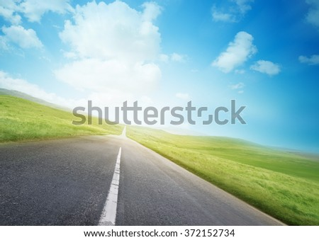 An open road through beautiful countryside. - stock photo