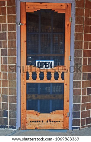 An Open Sign On An Old Fashioned Wood Framed Screen Door Beckons Passersby  To Enter.